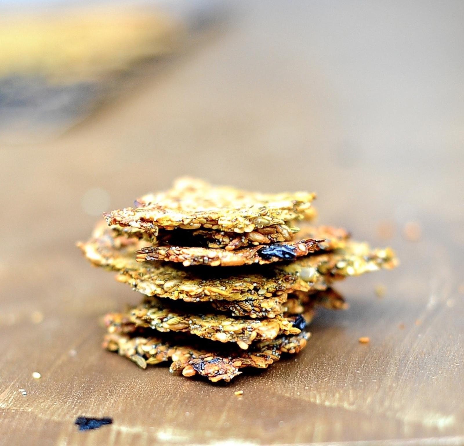 Seeded rosemary crackers stacked on a wood board