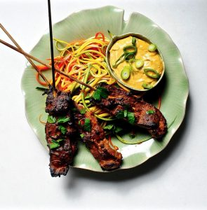 Vegan Seitan Satay with Spicy Peanut Sauce on green plate