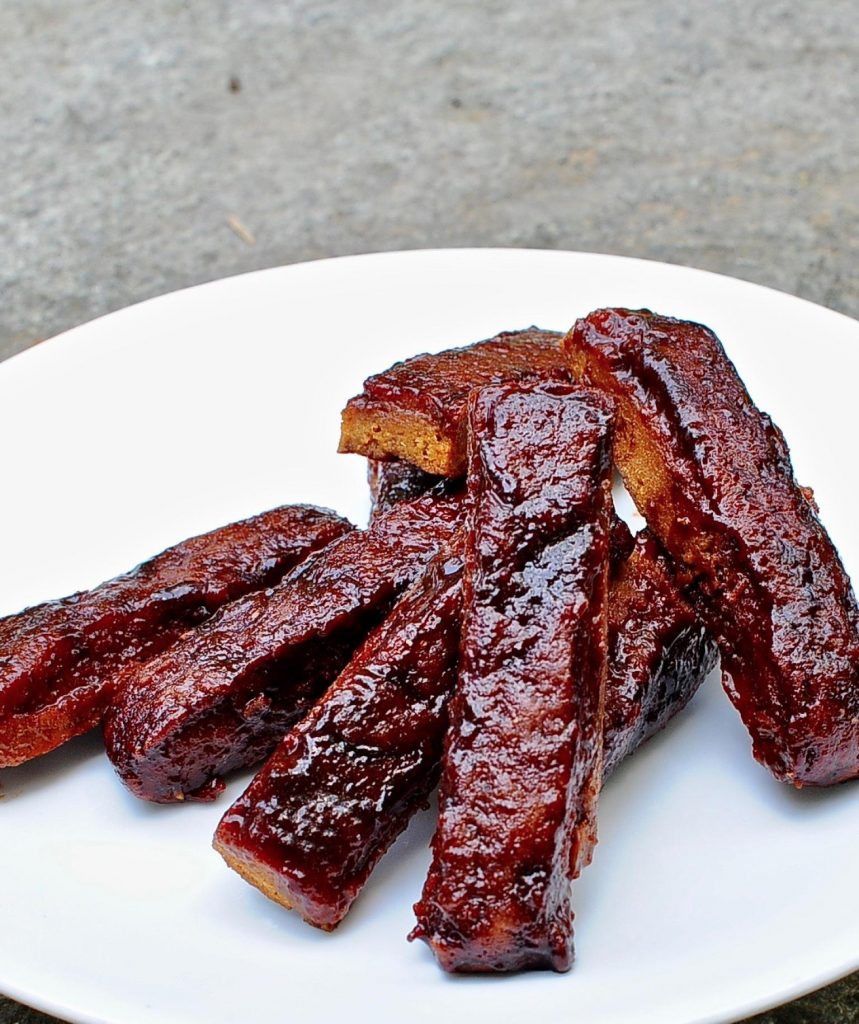 a pile of seitan ribs on a white plate.