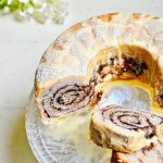 Classic vegan Babka with orange glaze on a glass cake stand.