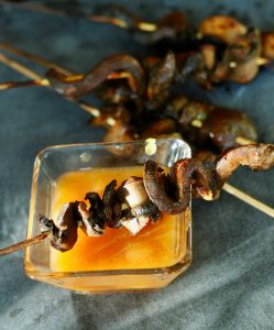 skewers of mushroom satay in glass bowl