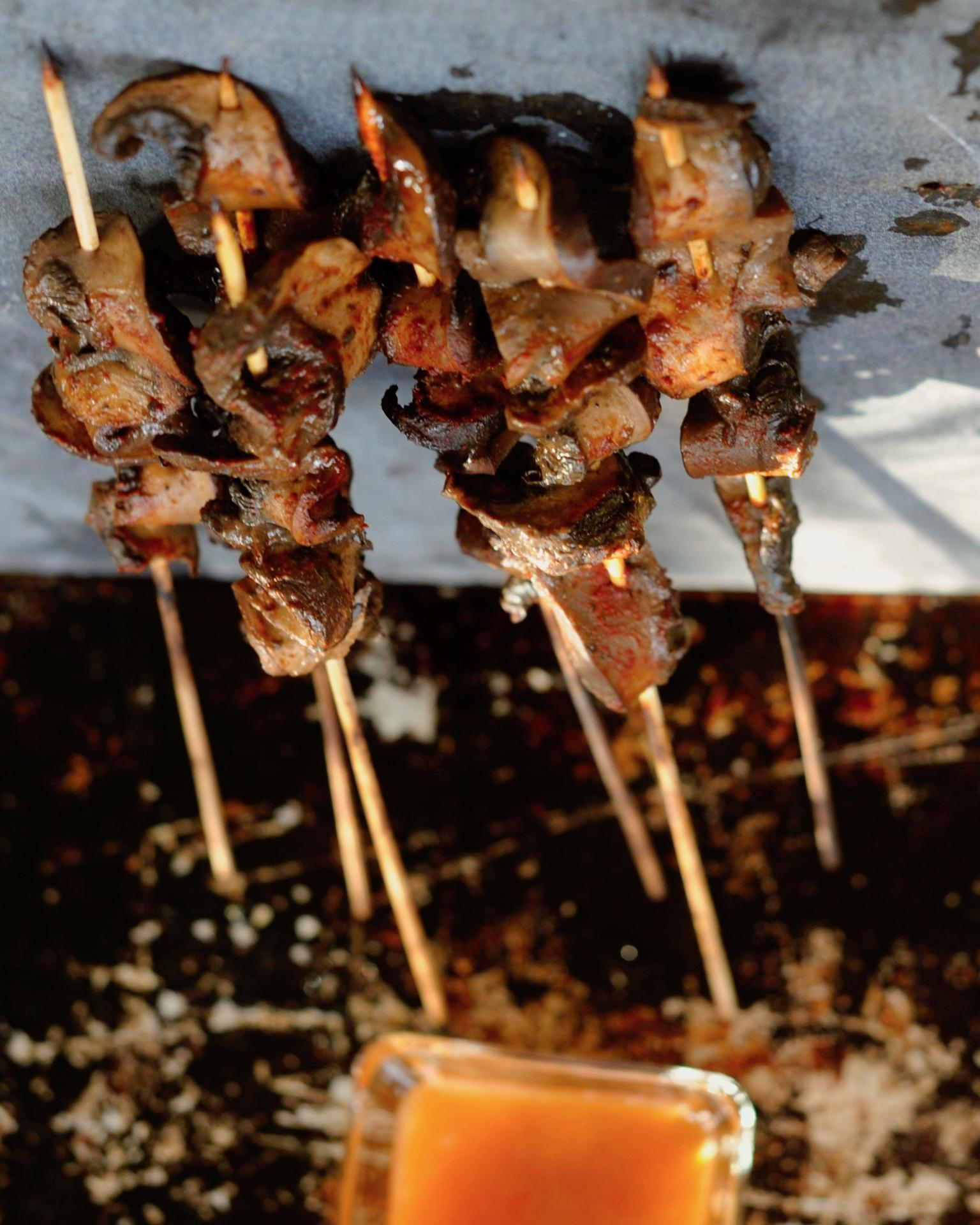 Mushroom satay skewers balanced on a baking sheet