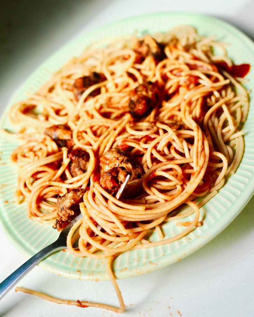 a forkful of  spaghetti on a green platter twined around