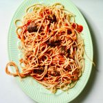Green Retro Platter with twirling spaghetti and sausage chunks.