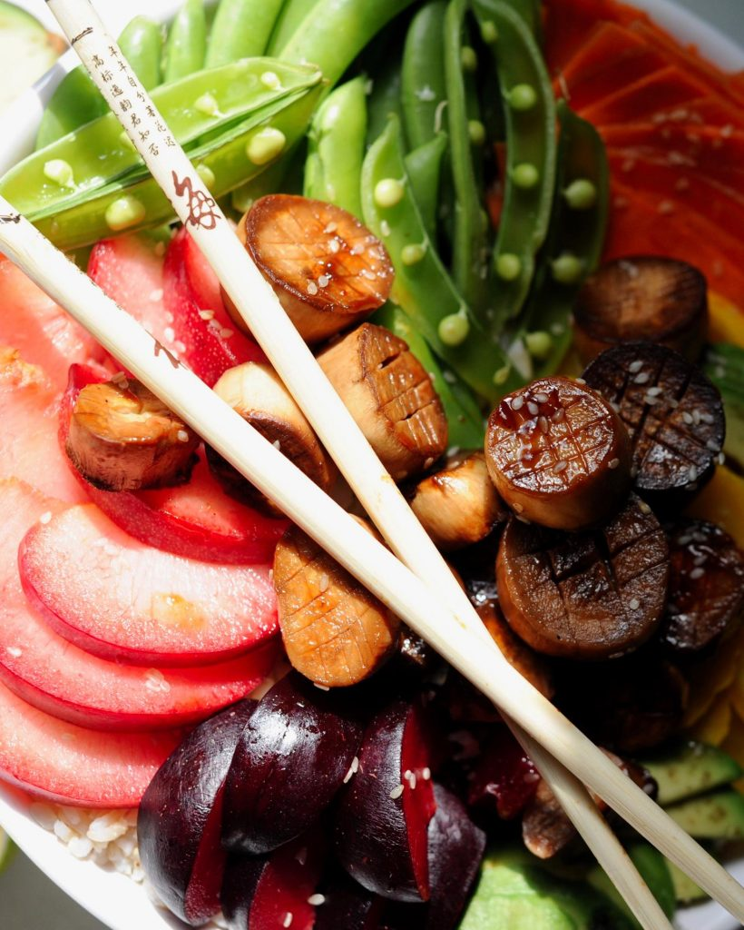 Chopsticks crossed over a white bowl filled with vegan mushroom scallops Poke