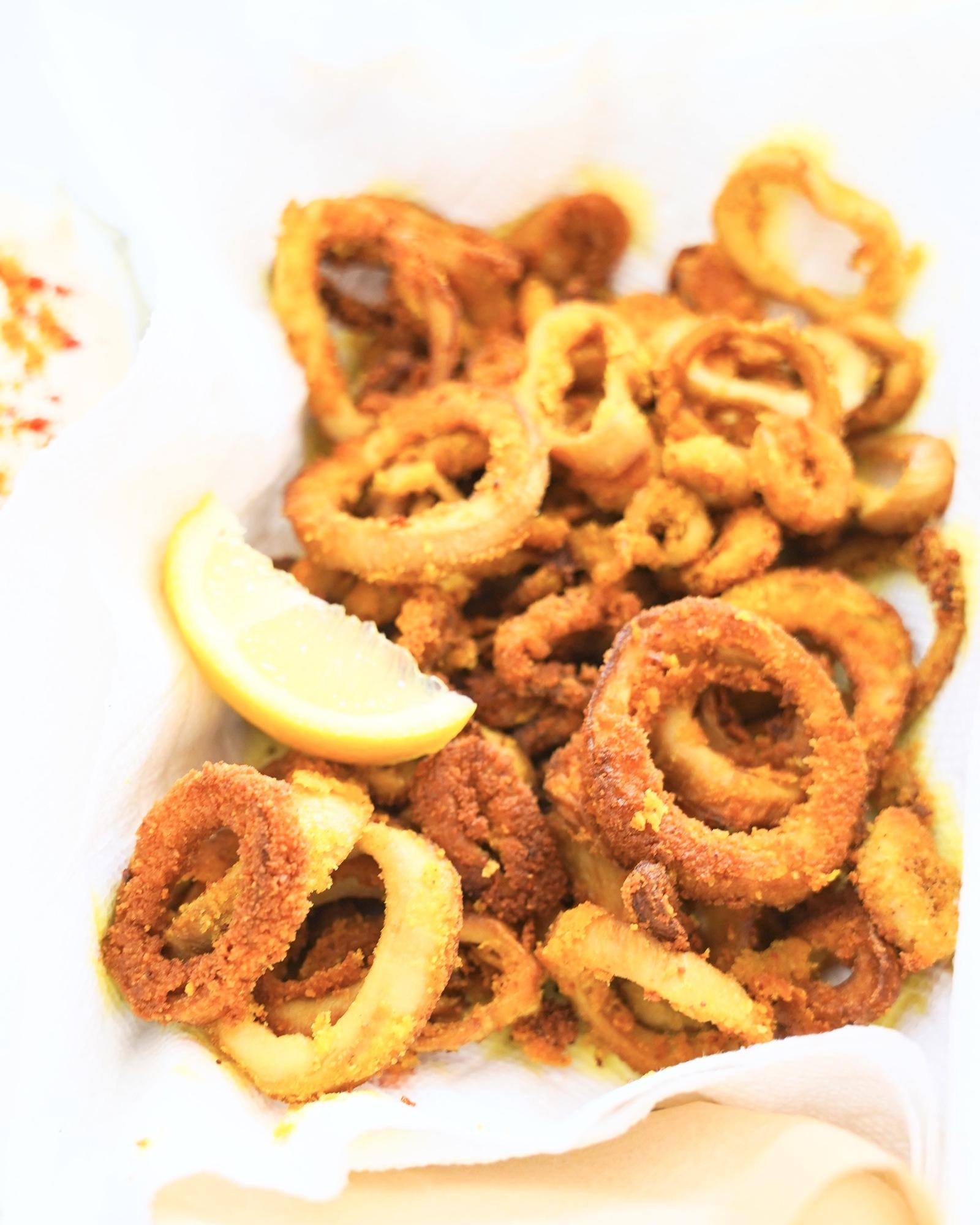 "A tray of crisp golden ""calamari"" rings with lemon slices"